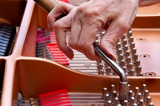 Man tuning a piano
